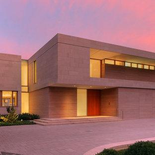Bild på ett stort funkis beige hus, med två våningar, blandad fasad och platt tak