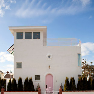White mediterranean two floor house exterior in New York with a flat roof.
