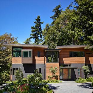 Modern inredning av ett stort flerfärgat hus, med tre eller fler plan, platt tak och levande tak