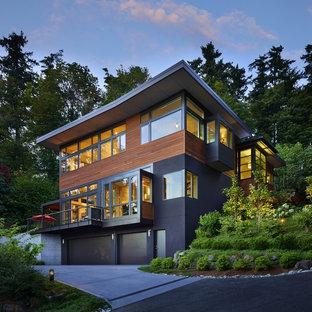 На фото: деревянный, большой, трехэтажный, разноцветный частный загородный дом в современном стиле с плоской крышей и зеленой крышей с
