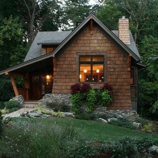 Foto della facciata di una casa piccola marrone rustica a due piani con rivestimento in legno e tetto a capanna