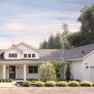 Foto della facciata di una casa unifamiliare grande bianca country a un piano con rivestimenti misti, tetto a mansarda e copertura a scandole