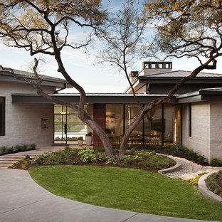 オースティンのコンテンポラリースタイルのおしゃれな平屋 (石材サイディング、グレーの外壁、寄棟屋根、戸建) の写真
