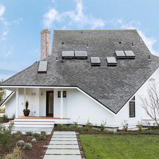 Ispirazione per la facciata di una casa bianca stile marinaro a due piani con rivestimento in legno e tetto a padiglione