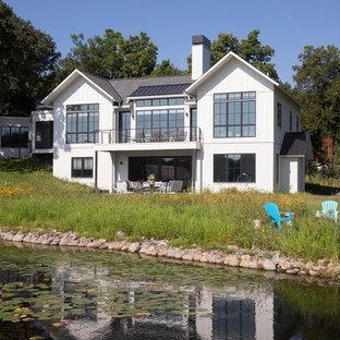 Ejemplo de fachada de casa blanca, costera, de dos plantas, con revestimiento de madera, tejado a dos aguas y tejado de teja de madera