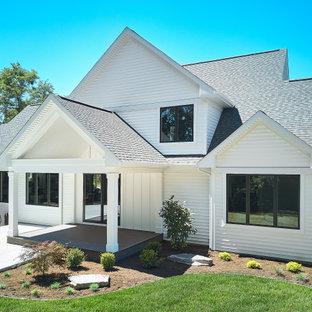 Пример оригинального дизайна: трехэтажный, белый частный загородный дом в стиле кантри с комбинированной облицовкой, двускатной крышей, крышей из гибкой черепицы, черной крышей и отделкой доской с нащельником