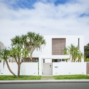 Design ideas for a white and large modern concrete house exterior in Sunshine Coast with three floors and a flat roof.