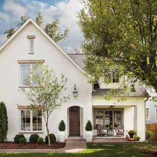 Modelo de fachada de casa blanca, tradicional renovada, grande, de dos plantas, con revestimiento de ladrillo, tejado de teja de madera y tejado a dos aguas