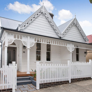 Mid-sized victorian one-storey white townhouse exterior in Sydney with wood siding and a gable roof.