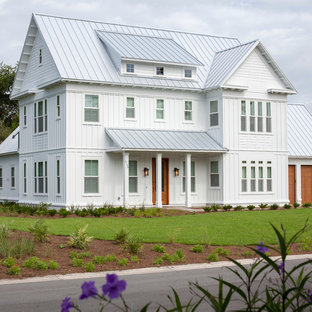 Example of a large farmhouse white three-story gable roof design in New York