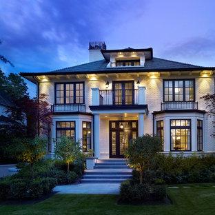 Imagen de fachada de casa blanca, clásica, grande, de dos plantas, con tejado a cuatro aguas, revestimiento de ladrillo y tejado de teja de madera