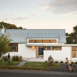 На фото: одноэтажный, белый частный загородный дом в современном стиле с двускатной крышей и металлической крышей