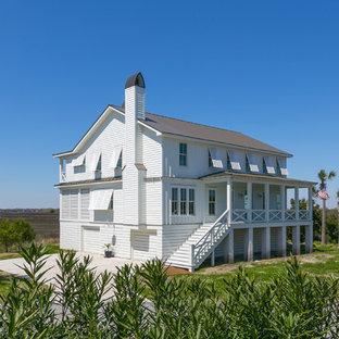 Immagine della facciata di una casa bianca tropicale a due piani con rivestimento in legno