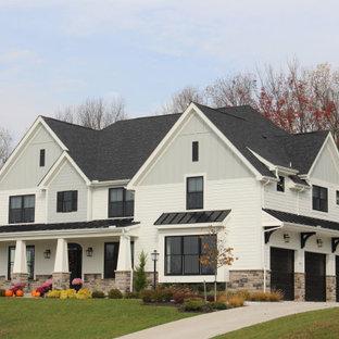 Amerikansk inredning av ett stort vitt hus, med två våningar, valmat tak och tak i shingel