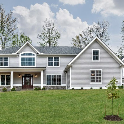 Large traditional gray two-story concrete fiberboard house exterior idea in Other with a hip roof and a shingle roof