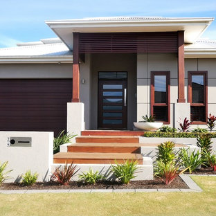 Photo of a mid-sized tropical one-storey beige house exterior in Sydney with a hip roof and a metal roof.