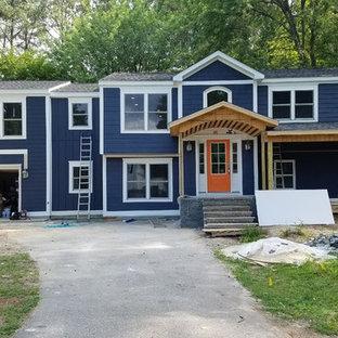 Imagen de fachada de casa azul, clásica, grande, a niveles, con revestimientos combinados, tejado a dos aguas y tejado de teja de madera