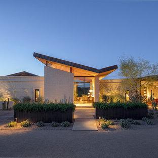 Идея дизайна: кирпичный, белый частный загородный дом в современном стиле с крышей-бабочкой