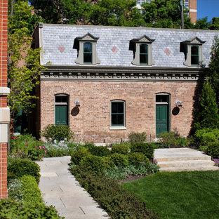 Aménagement d'une façade de maison rouge classique à un étage avec un toit en tuile.