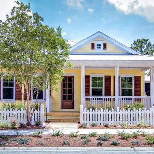 Mid-sized coastal yellow one-story vinyl gable roof photo in Jacksonville