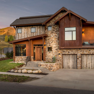 Mid-sized mountain style brown two-story mixed siding exterior home photo in Denver with a mixed material roof
