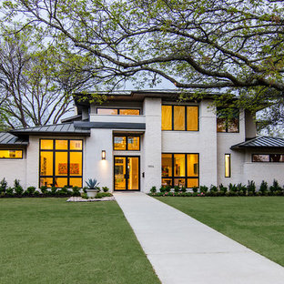 Example of a large trendy white two-story brick exterior home design in Dallas with a hip roof