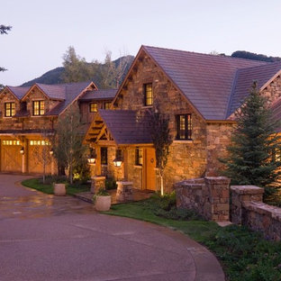 Expansive arts and crafts two-storey brown house exterior in Denver with stone veneer and a shingle roof.