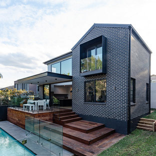 Inspiration for a large contemporary two-storey brick black house exterior in Sydney with a gable roof and a metal roof.