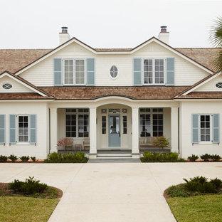 Diseño de fachada de casa blanca, marinera, extra grande, de dos plantas, con revestimiento de ladrillo, tejado a cuatro aguas y tejado de teja de madera