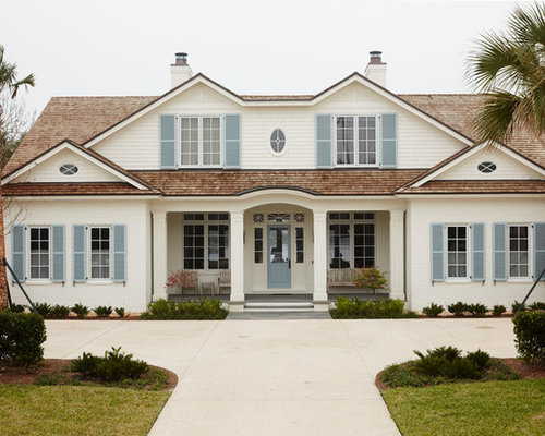 Huge coastal white two story brick exterior home photo in jacksonville with a hip roof