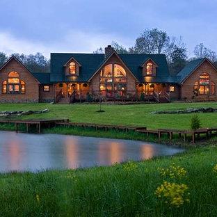 Imagen de fachada marrón, rústica, grande, de dos plantas, con revestimiento de madera y tejado a dos aguas