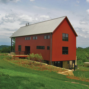 Photo of a red and large rural two floor detached house in Other with wood cladding, a pitched roof and a metal roof.