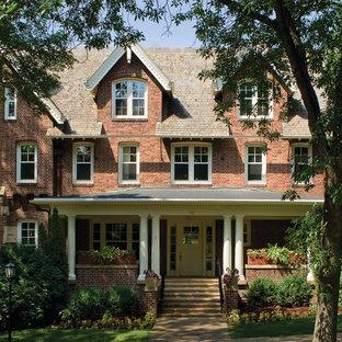 Foto de fachada de casa roja, clásica, extra grande, de tres plantas, con revestimiento de ladrillo, tejado a dos aguas y tejado de teja de madera