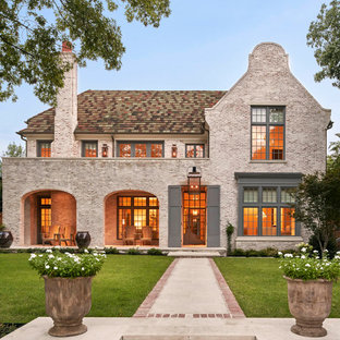 Large traditional brown two-story brick house exterior idea in Dallas with a hip roof and a shingle roof