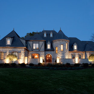 Huge traditional beige two-story stone exterior home idea in Orlando with a hip roof and a shingle roof