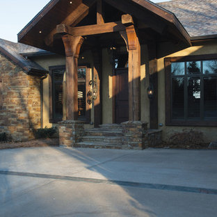 Example of a large mountain style brown one-story stone exterior home design in Other