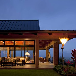 Example of a large island style beige one-story glass house exterior design in Hawaii with a hip roof and a metal roof