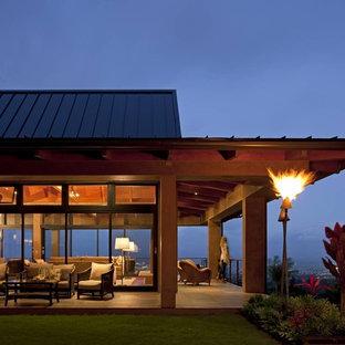 Esempio della facciata di una casa unifamiliare grande beige tropicale a un piano con rivestimento in vetro, tetto a padiglione e copertura in metallo o lamiera
