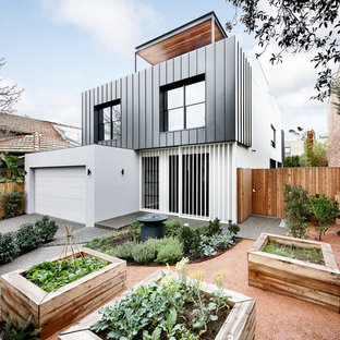 Design ideas for a large contemporary grey house exterior in Melbourne with mixed siding, a flat roof, three or more storeys and a metal roof.