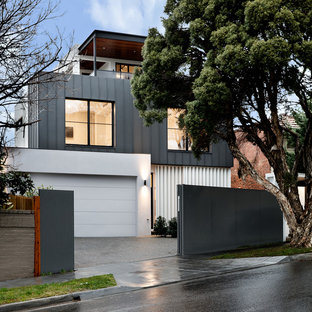 Photo of a large contemporary grey house exterior in Melbourne with three or more storeys, mixed siding, a flat roof and a metal roof.
