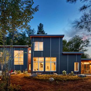 Foto på ett stort rustikt blått hus, med två våningar, fiberplattor i betong och platt tak