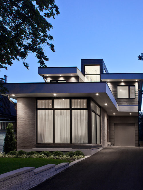 Example of a mid-sized trendy gray two-story brick exterior home design in