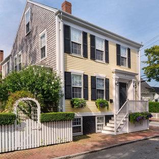 Idéer för ett mellanstort klassiskt gult hus, med tre eller fler plan, vinylfasad och sadeltak