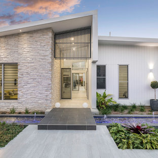 This is an example of a contemporary one-storey white house exterior in Brisbane with mixed siding and a shed roof.