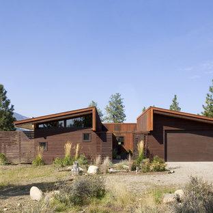 Modelo de fachada marrón, moderna, de tamaño medio, de una planta, con revestimiento de metal y tejado de un solo tendido