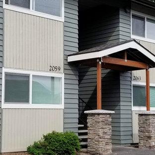ポートランドのおしゃれな家の外観 (木材サイディング、緑の外壁、切妻屋根、アパート・マンション、板屋根) の写真