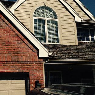 Modelo de fachada tradicional, de dos plantas, con revestimiento de ladrillo y tejado a dos aguas