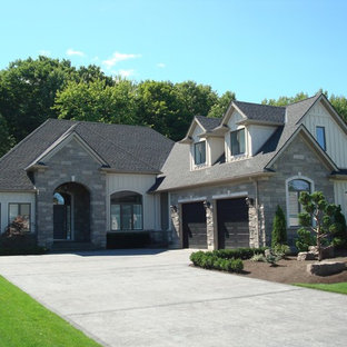 Inspiration for a large transitional gray one-story stone exterior home remodel in Toronto with a shed roof