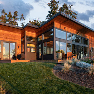 Example of a mid-sized minimalist brown one-story mixed siding house exterior design in Seattle with a shed roof and a metal roof