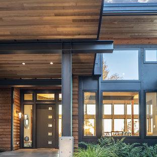 Ejemplo de fachada de casa marrón, minimalista, de tamaño medio, de una planta, con revestimientos combinados, tejado de un solo tendido y tejado de metal